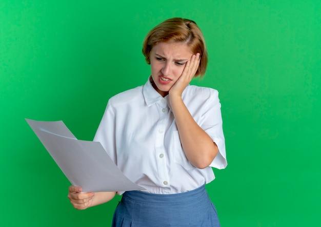Jonge boos blonde russische meisje legt hand op gezicht kijken naar vellen papier