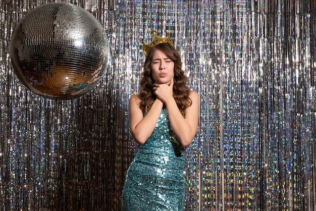 Jonge boos charmante dame draagt blauwgroene glanzende jurk met pailletten met kroon in het feest