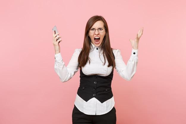 Jonge boos geïrriteerde zakenvrouw in glazen schreeuwen met mobiele telefoon verspreiden handen geïsoleerd op roze achtergrond. dame baas. prestatie carrière rijkdom concept. kopieer ruimte voor advertentie.