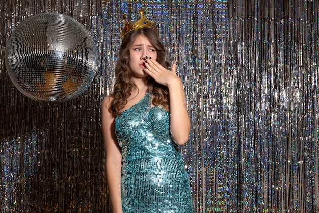 Jonge boos mooie dame draagt blauwgroene glanzende jurk met pailletten met kroon in het feest