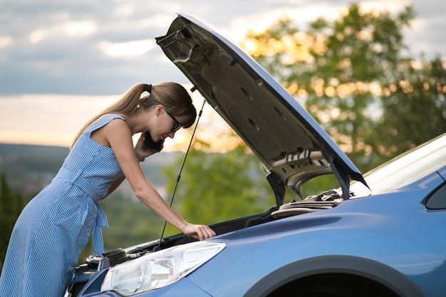 Jonge boos vrouwenbestuurder die op mobiele telefoon spreekt dichtbij een kapotte auto met open kap die motor inspecteert die problemen met haar voertuig heeft.