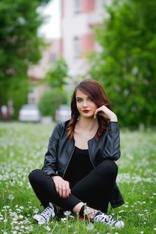 Jonge bosnische vrouw zittend op het gras met paardebloemen om haar heen in het park