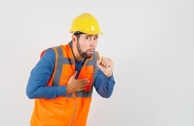 Jonge bouwer die aan hoest in overhemd, vest, helm lijdt en onwel kijkt. vooraanzicht.