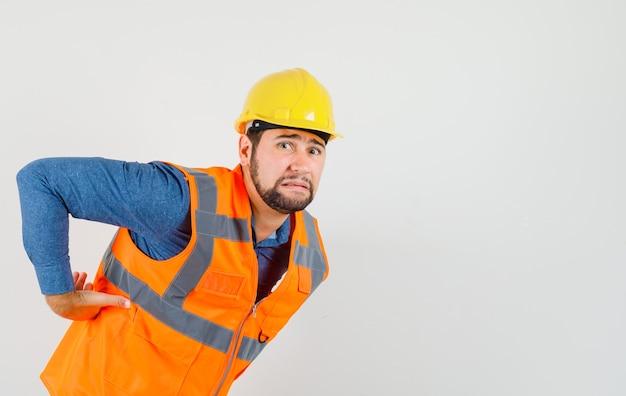 Jonge bouwer die aan rugpijn in overhemd, vest, helm lijdt en vermoeid, vooraanzicht kijkt.