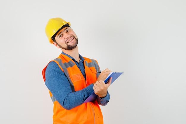 Jonge bouwer die aantekeningen maakt op klembord in overhemd, vest, helm en vrolijk, vooraanzicht kijkt.