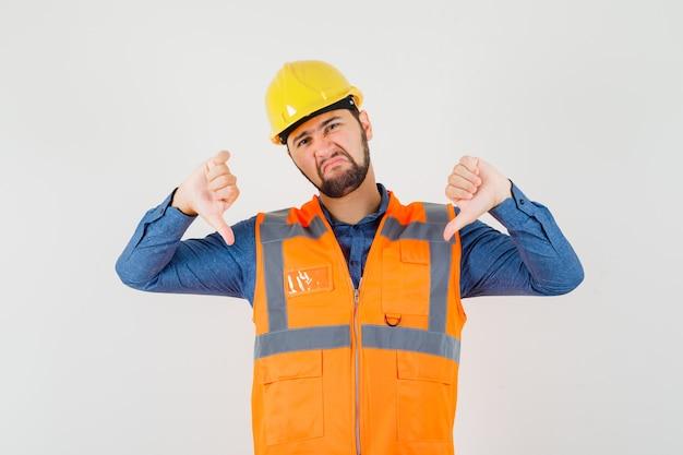Jonge bouwer die dubbele duimen neer in overhemd, vest, helm toont en ontevreden kijkt. vooraanzicht.