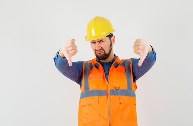 Jonge bouwer die dubbele duimen neer in overhemd, vest, helm toont en teleurgesteld, vooraanzicht kijkt.