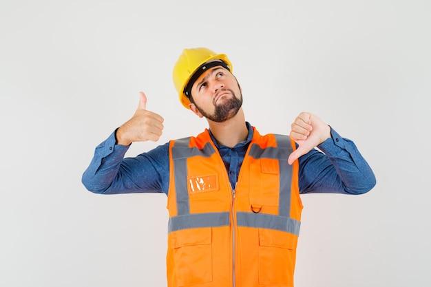 Jonge bouwer die duimen op en neer in overhemd, vest, helm toont en aarzelend kijkt. vooraanzicht.