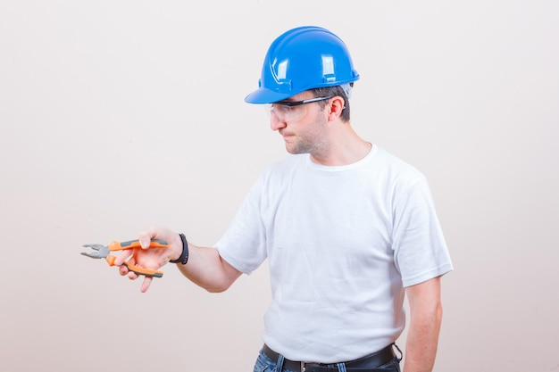 Jonge bouwer die een tang vasthoudt in een t-shirt, jeans, helm en er zelfverzekerd uitziet