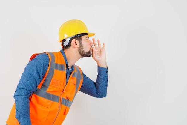 Jonge bouwer die heerlijk gebaar in overhemd, vest, helm toont en verrukt kijkt. .