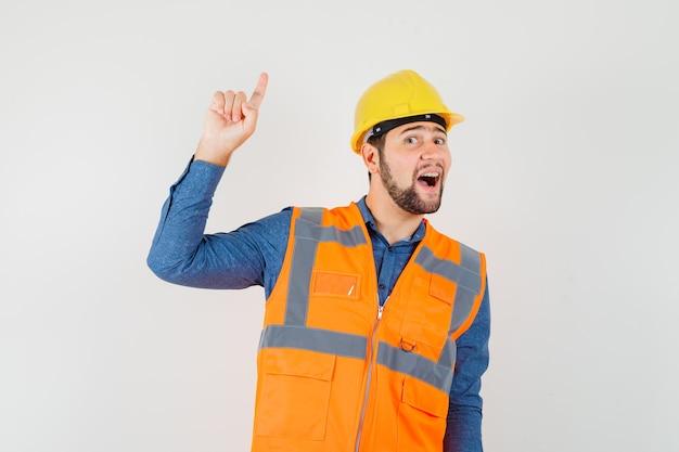 Jonge bouwer die in overhemd, vest, helm benadrukt en vrolijk kijkt. vooraanzicht.