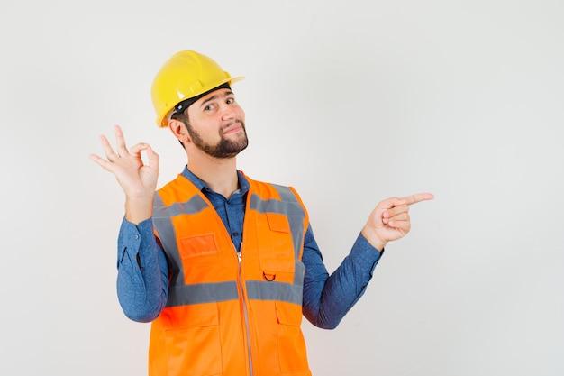 Jonge bouwer die ok teken toont, naar de kant wijst in overhemd, vest, helm en vrolijk kijkt. vooraanzicht.