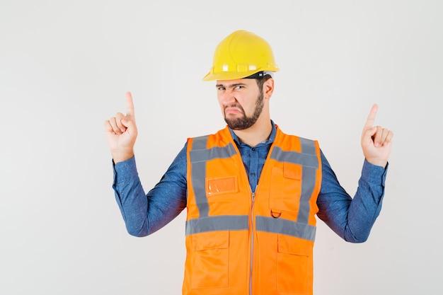 Jonge bouwer die vingers in overhemd, vest, helm benadrukt en somber, vooraanzicht kijkt.