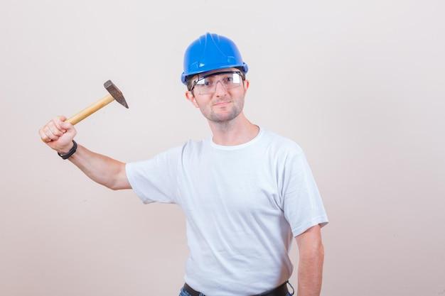 Jonge bouwer dreigt met hamer in t-shirt, helm en kijkt geamuseerd