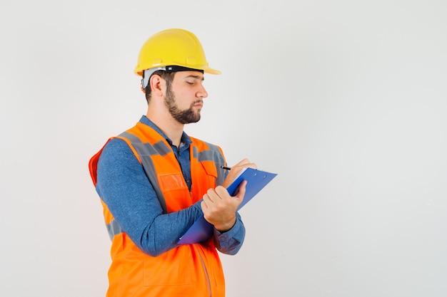 Jonge bouwer in overhemd, vest, helm die aantekeningen op klembord maakt en druk, vooraanzicht kijkt.