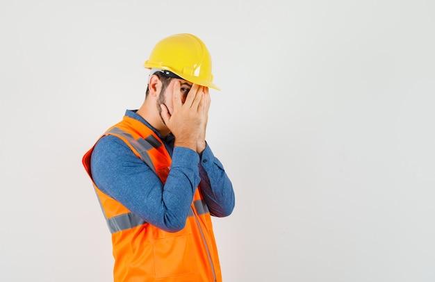 Jonge bouwer in overhemd, vest, helm die door vingers kijkt en bang, vooraanzicht kijkt.