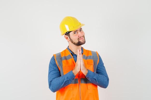 Jonge bouwer in overhemd, vest, helmholding dient biddend gebaar in en kijkt optimistisch, vooraanzicht.