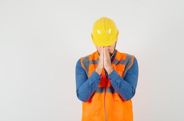 Jonge bouwer in shirt, vest, helm hand in hand in gebed gebaar en op zoek kalm, vooraanzicht.