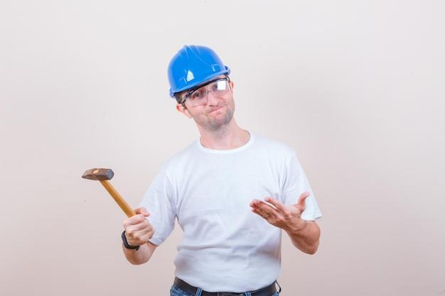Jonge bouwer in t-shirt, spijkerbroek, helm die hamer toont en er teleurgesteld uitziet