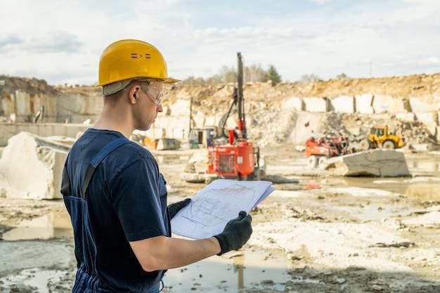 Jonge bouwer in werkkleding met schets van constructie
