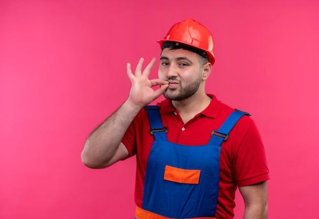 Jonge bouwer man in bouw uniform en veiligheidshelm stilte gebaar maken zoals mond sluiten met rits