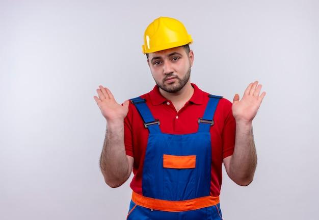 Jonge bouwer man in bouw uniform en veiligheidshelm verhogen handen in overgave met droevige uitdrukking