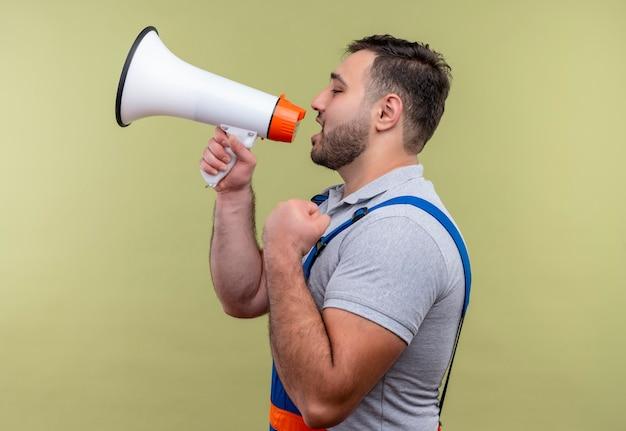 Jonge bouwer man in bouw uniform schreeuwen naar megafoon