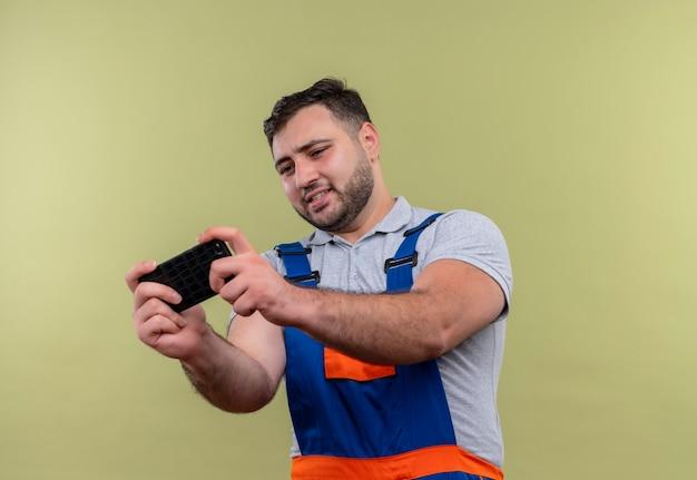 Jonge bouwer man in bouw uniform speelspel op zijn smartphone