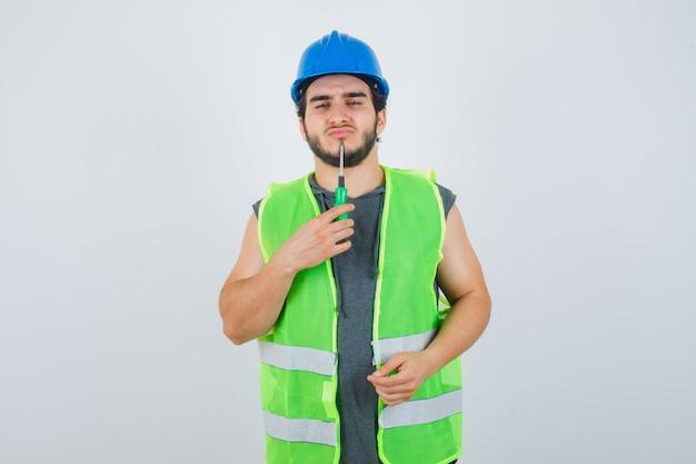 Jonge bouwer man in uniform houden puntje van schroevendraaier op kin en op zoek doordachte, vooraanzicht.