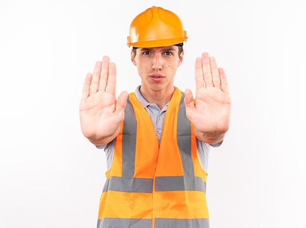 Jonge bouwer man in uniform weergegeven: stop gebaar geïsoleerd op een witte muur