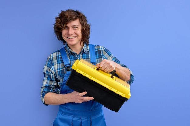 Jonge bouwer man in werkkleding gereedschapskist in handen houdt en kijkt naar camera glimlachend geïsoleerd op paarse achtergrond.