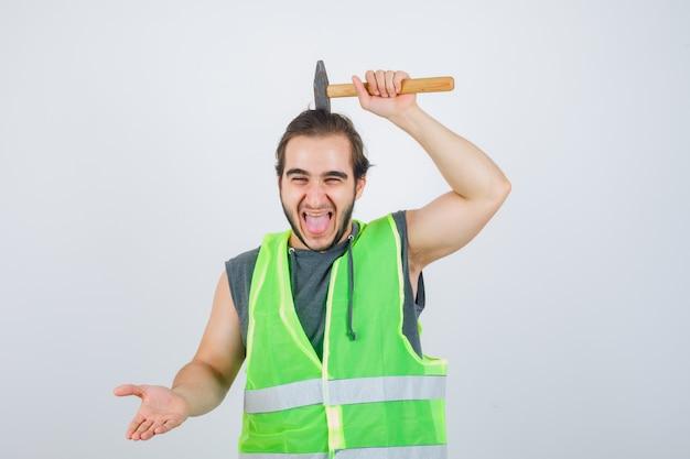 Jonge bouwer man met hamer boven het hoofd terwijl tong uitsteekt in uniform van werkkleding en er grappig uitziet. vooraanzicht.