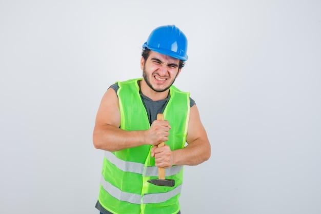 Jonge bouwer man met hamer in uniforme werkkleding en op zoek naar sterker. vooraanzicht.