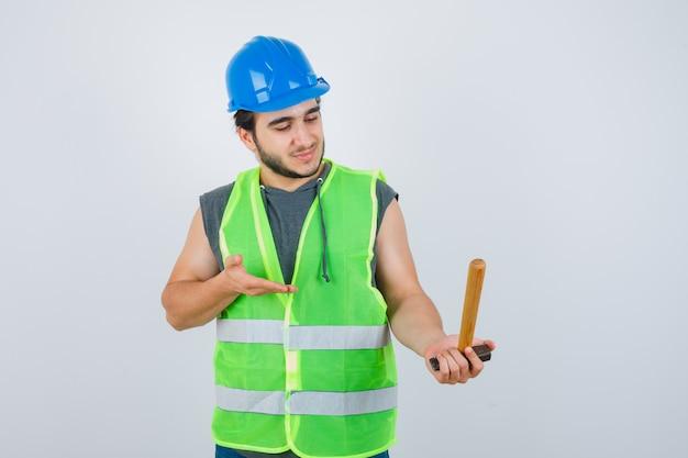 Jonge bouwer man met hamer in uniforme werkkleding en op zoek vrolijk. vooraanzicht.