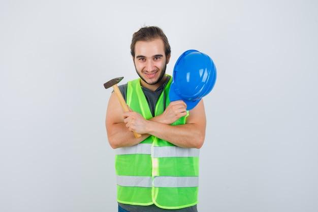 Jonge bouwer man met helm en hamer terwijl het kruisen van de armen op de borst in uniform van werkkleding en er vrolijk uitziet. vooraanzicht.