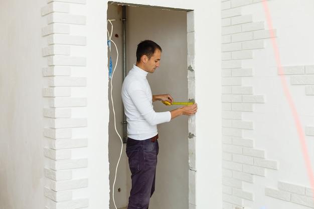 Jonge bouwer met geel meetlint op echte bouwplaats, selectieve focus, natuurlijk zacht licht