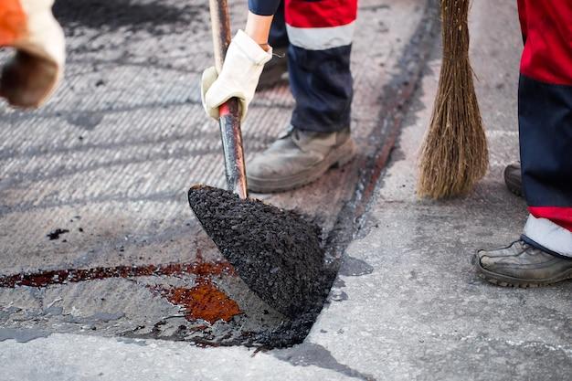 Jonge bouwer op asfaltering bestratingsafwerkmachines machine tijdens straat reparatie werkzaamheden