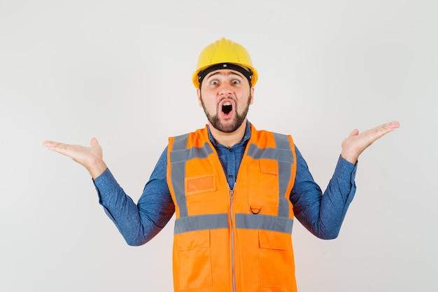 Jonge bouwer schalen gebaar maken in shirt, vest, helm en op zoek verrast, vooraanzicht.