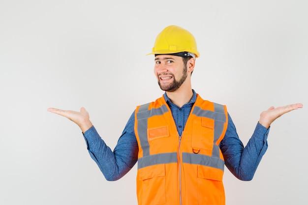 Jonge bouwer schalen gebaar maken in shirt, vest, helm en op zoek vrolijk, vooraanzicht.