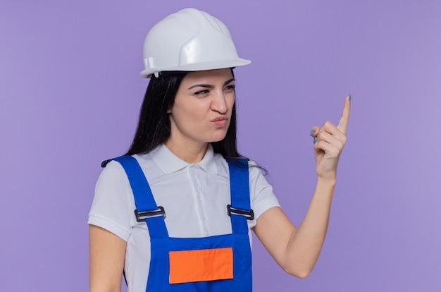 Jonge bouwer vrouw in bouw uniform en veiligheidshelm op zoek opzij verward en ontevreden met opgeheven arm