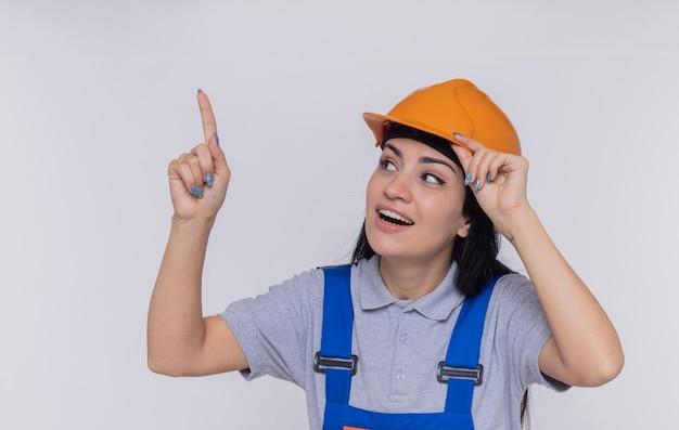 Jonge bouwer vrouw in bouw uniform en veiligheidshelm opzoeken glimlachend wijzend met wijsvinger naar iets
