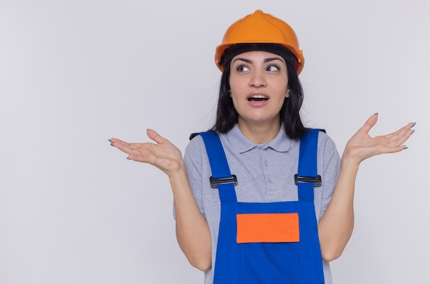 Jonge bouwer vrouw in bouw uniform en veiligheidshelm opzoeken verward spreidende armen naar de zijkanten