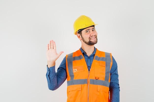 Jonge bouwer zwaaiende hand om hallo of tot ziens in overhemd, vest, helm te zeggen en blij te kijken. vooraanzicht.