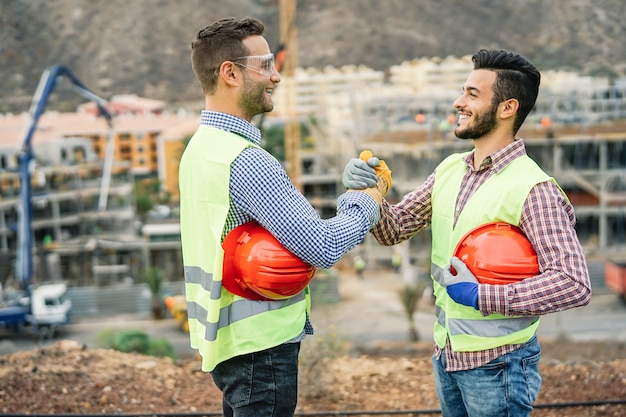 Jonge bouwers die handen schudden die een overeenkomst over bouwwerf maken