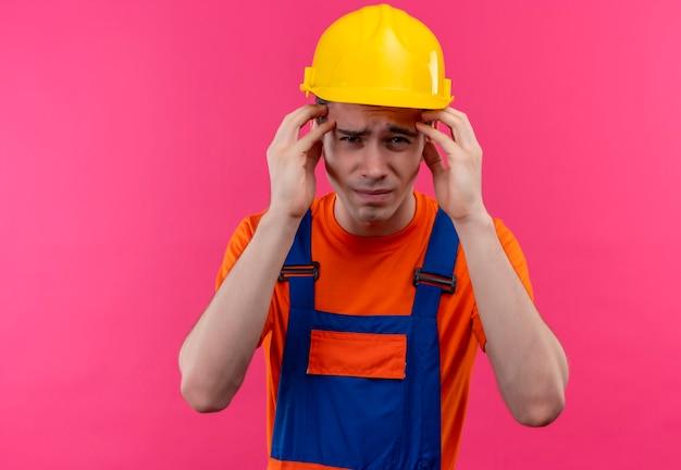 Jonge bouwersmens die bouwuniform en veiligheidshelm draagt, is het zat