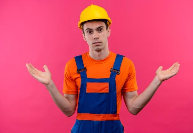 Jonge bouwersmens die bouwuniform en veiligheidshelm draagt, is in de war