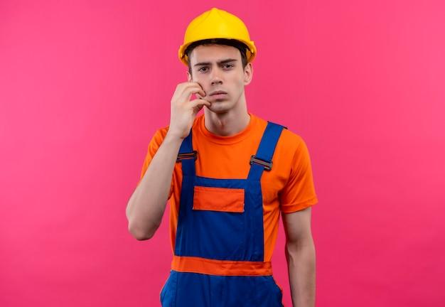 Jonge bouwersmens die bouwuniform en veiligheidshelm draagt, wrijft zijn gezicht met zijn linkerhand