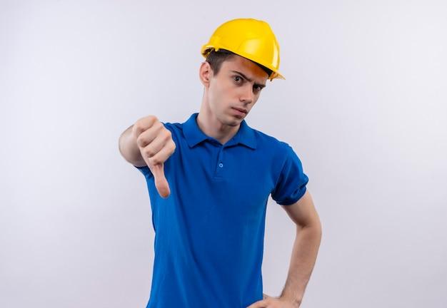 Jonge bouwersmens die bouwuniform en veiligheidshelm dragen die boze duimen naar beneden doen