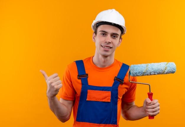 Jonge bouwersmens die bouwuniform en veiligheidshelm dragen die gelukkige duimen doen en een rolborstel houden