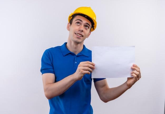 Jonge bouwersmens die bouwuniform en veiligheidshelm dragen houdt een document